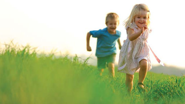 healthy children running through tall grass