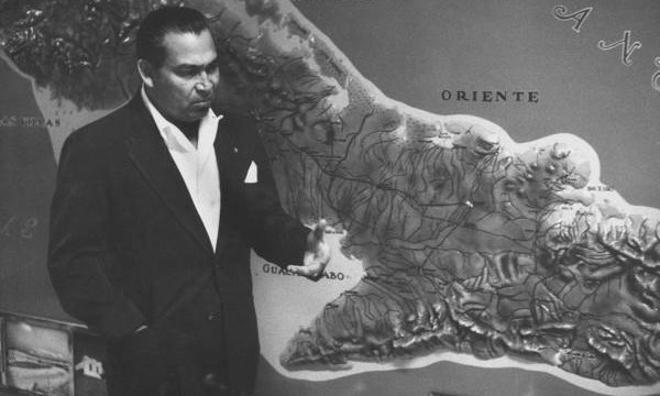 Batista standing beside map of the Sierra Maestra mountains