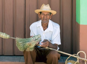Broom vendor at doorstep in Trinidad, Cuba