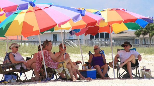 Beach goers lounging beneath umbrellas