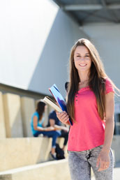 portrait of attractive cheerful young student woman outdoor in front of high school campus
