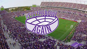 fans donning purple fill the stadium